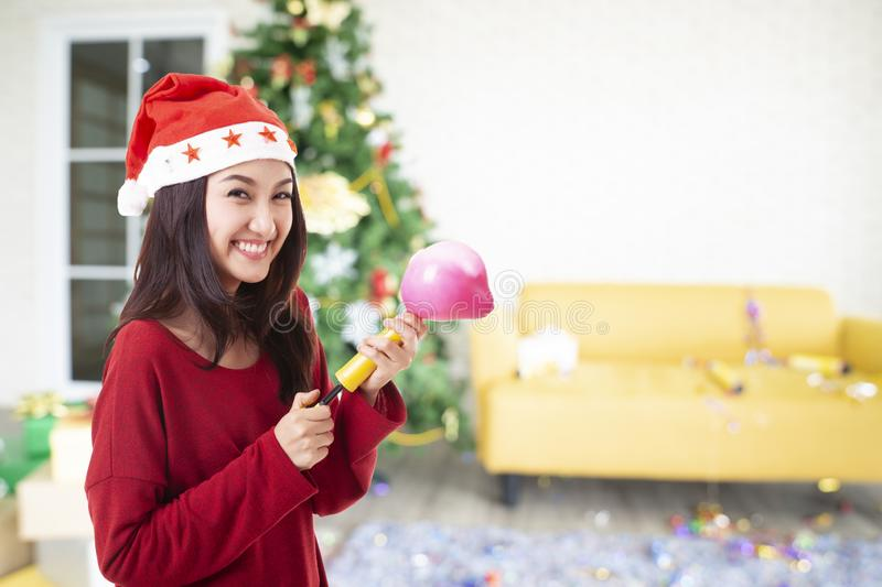 Beautiful asian woman wearing a Santa Claus hat smiling happily on Christmas tree background royalty free stock images
