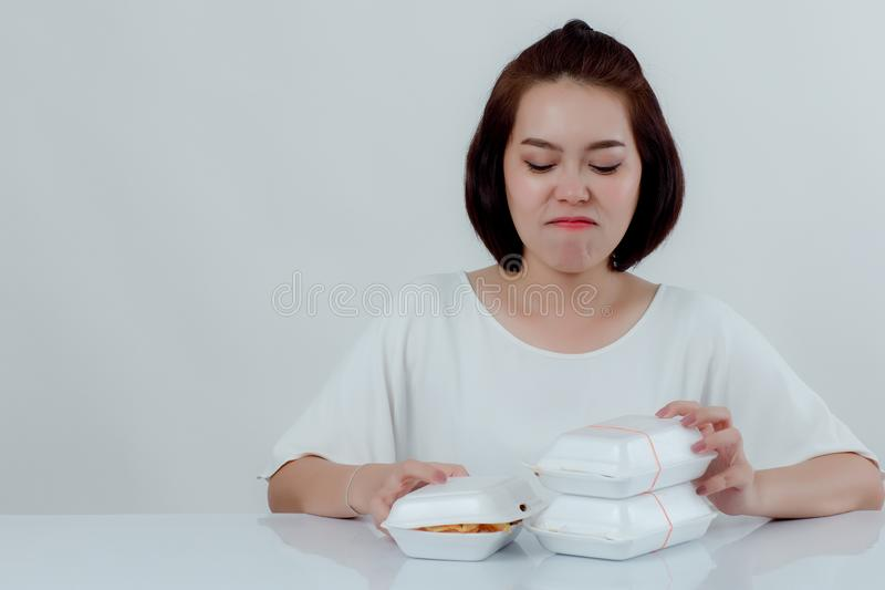 Beautiful Asian woman, white shirt Sitting in front of the dining table There is an expression of disgust in the foam box. Do not stock photos