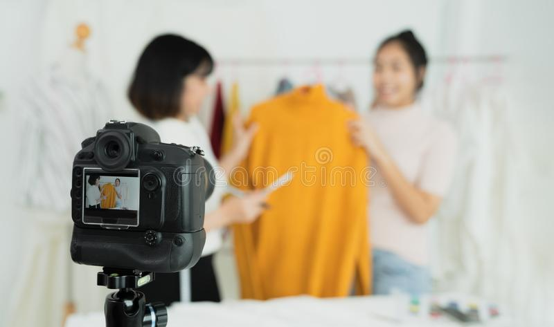 Beautiful asian woman blogger showing clothes in front of camera to recording vlog video live streaming at her shop. Business onli stock images