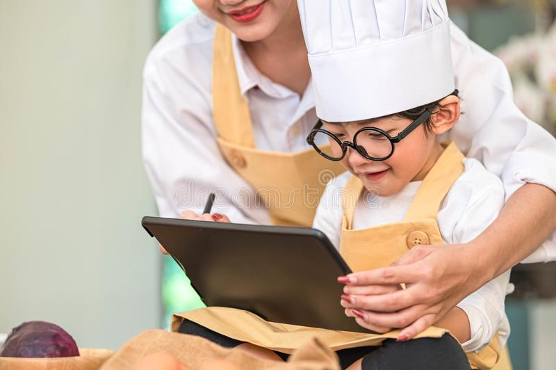 Beautiful Asian woman and cute little boy prepare online shopping and listing ingredient for cooking in kitchen at home with stock images