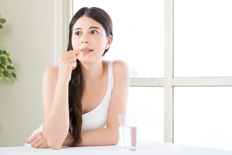 Beautiful asian women eating vitamin pill for health care. Beautiful asian woman eating vitamin pill for health care at home royalty free stock photo