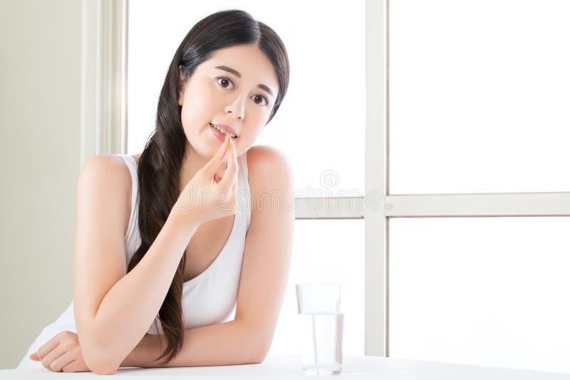 Beautiful asian women eating vitamin pill for health care. Beautiful asian woman eating vitamin pill for health care at home royalty free stock photography