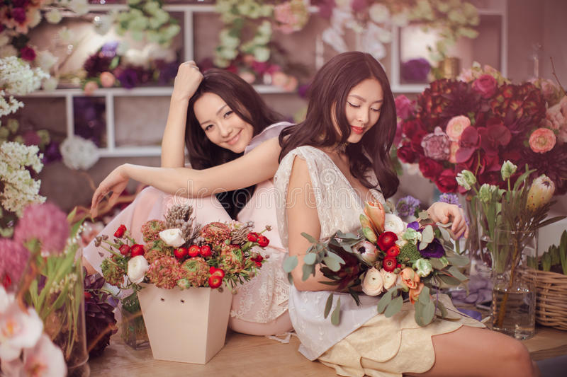 Beautiful asian women florists happy working in flower store with a lot of spring flowers stock photos