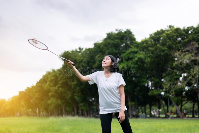 Beautiful asian woman playing badminton in nature in the morning,Happy and smiling stock photography