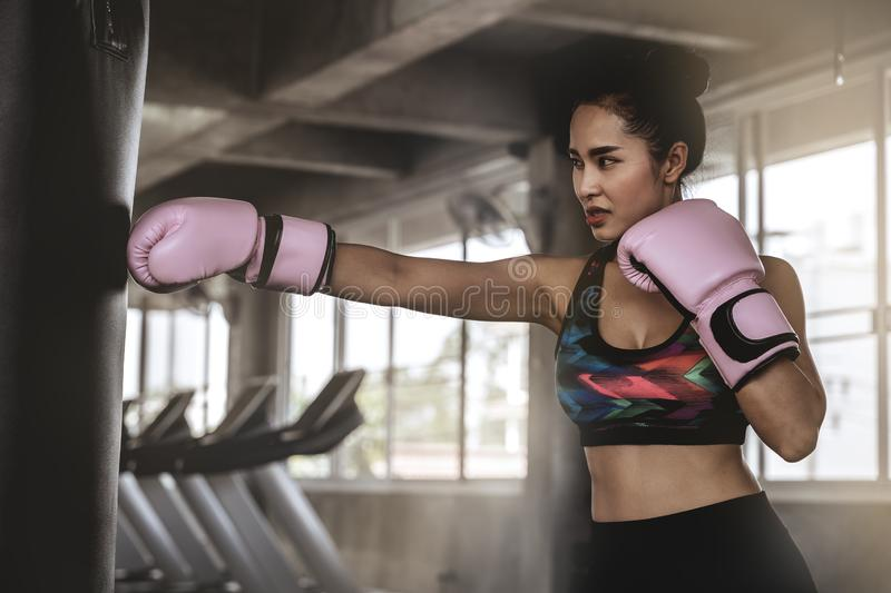 Beautiful Asian women are punching sandbags in the gym, exercise ideas, weight loss, muscle building royalty free stock photos