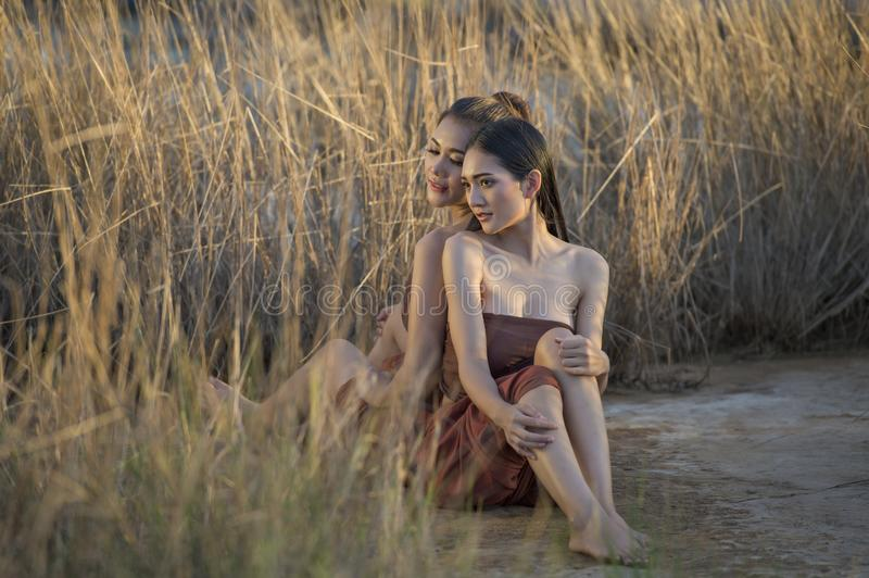 Beautiful Asian women sitting in grass field wearing Thai tradition in evening royalty free stock photography