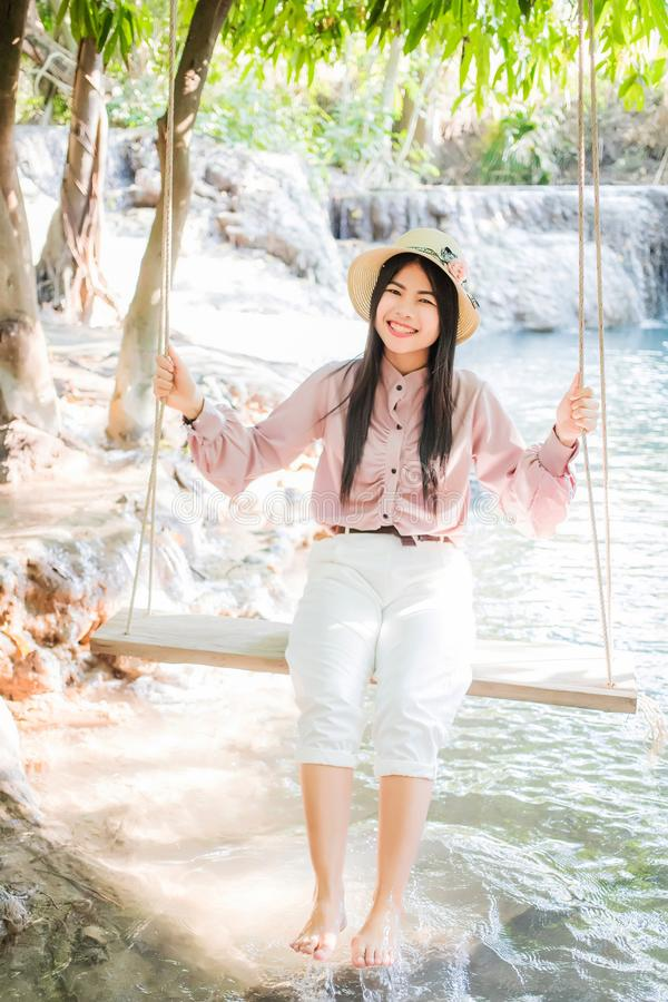 Beautiful Asian women, Thai people, wearing pink casual clothes with a refreshing and smiling face are sitting on the swings. stock photos