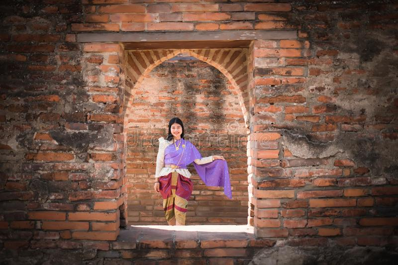 Beautiful Asian women, Thai people wearing Thai clothes, standing on the old wall. stock images