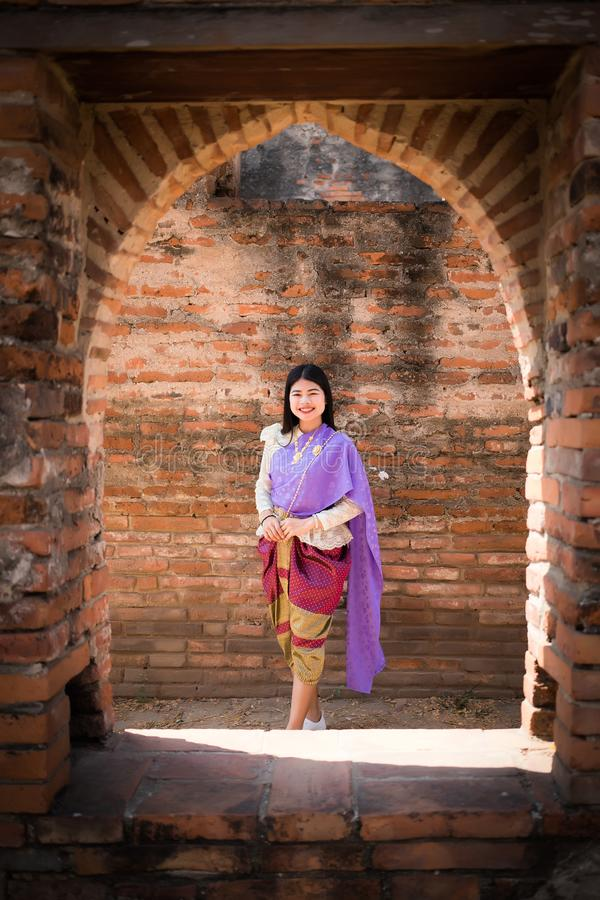 Beautiful Asian women, Thai people wearing Thai clothes, standing on the old wall. royalty free stock image
