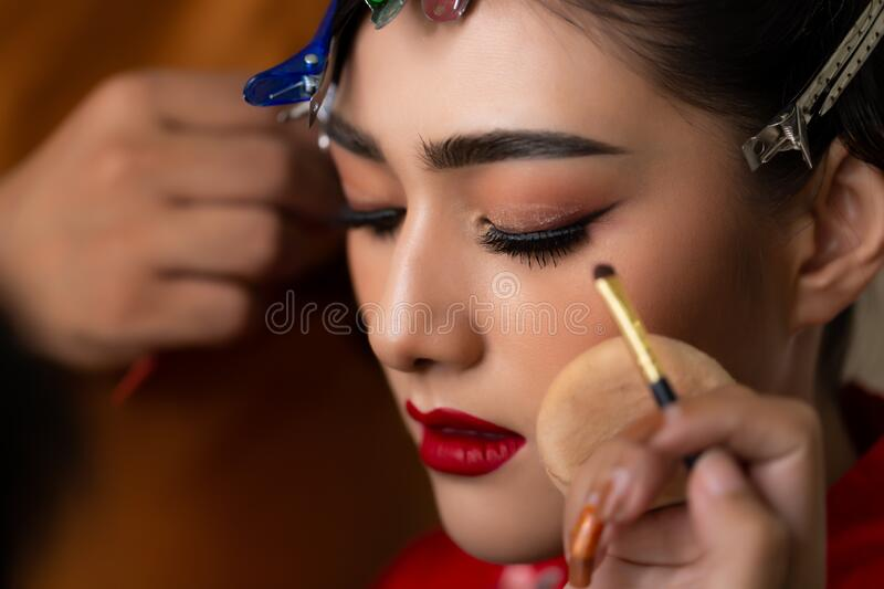 Beautiful asian young bride apply beautiful makeup and hairdo by makeup artist, hairstylist for wedding ceremony. Attractive asian stock image
