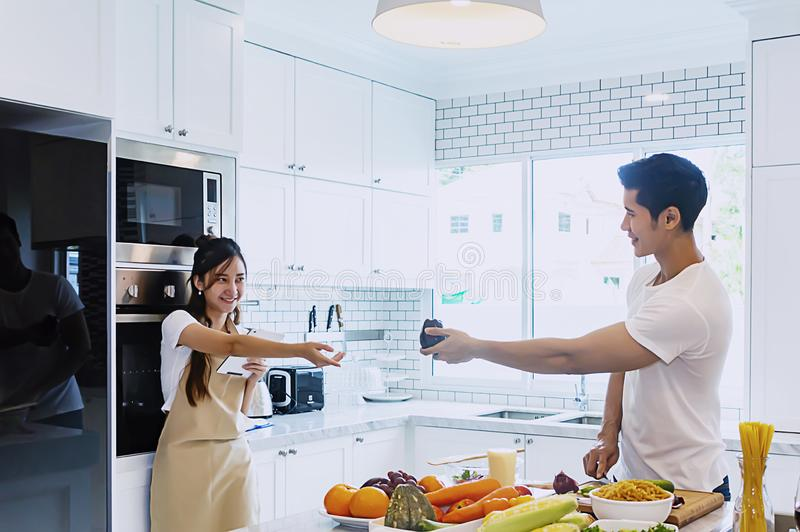 Beautiful asian young couple loving smiling is looking to cooking in kitchen at home stock photos