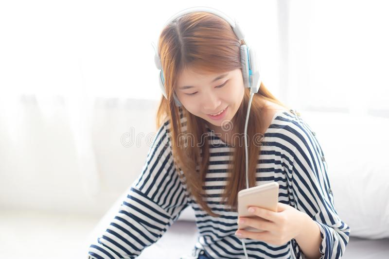 Beautiful asian young woman enjoy listen music with headphone and holding smart mobile phone while sitting in bedroom, relax girl royalty free stock photo