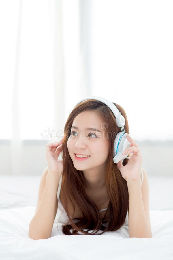Beautiful asian young woman enjoy listen music with headphone while lying in bedroom. royalty free stock photos