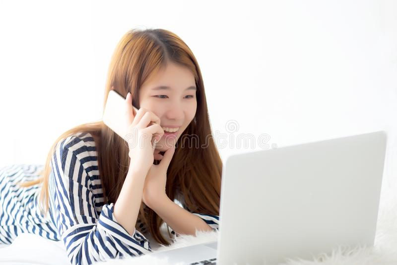 Beautiful asian young woman lying on bed using laptop and talking mobile smart phone at bedroom for leisure and relax royalty free stock image