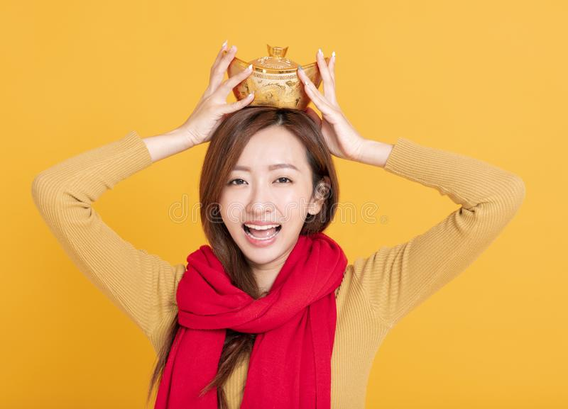 Beautiful asian young woman showing chinese gold ingot and celebrating new year. chinese text : rich and lucky stock photography
