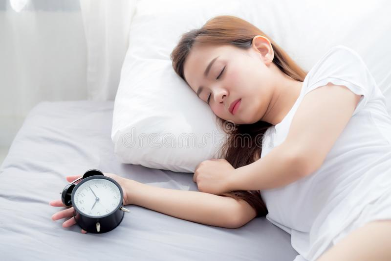 Beautiful asian young woman turn off alarm clock in good morning, wake up for sleep. Beautiful asian young woman turn off alarm clock in good morning, wake up stock images