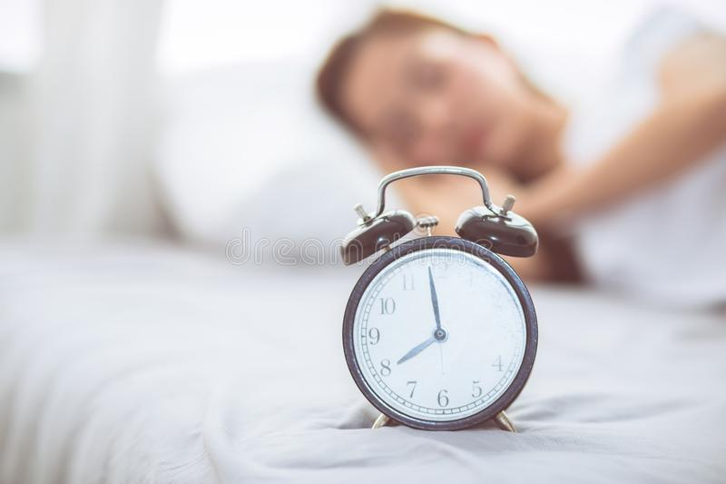 Beautiful asian young woman turn off alarm clock in good morning, wake up for sleep with closeup foreground alarm clock. Relax and lifestyle concept royalty free stock images