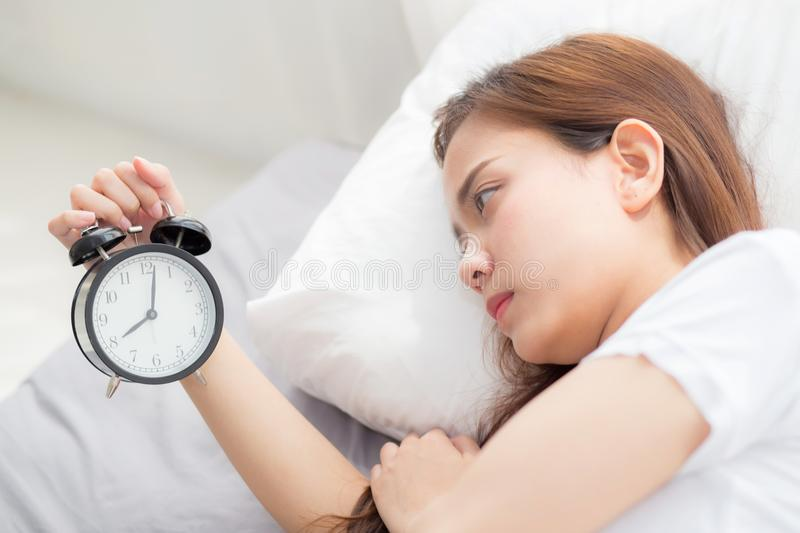 Beautiful asian young woman turn off alarm clock in good morning, wake up for sleep with closeup foreground alarm clock. Beautiful asian young woman turn off royalty free stock photos