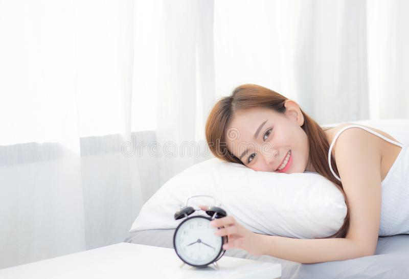 Beautiful asian young woman turn off alarm clock in morning, wake up for sleep with alarm clock. stock image