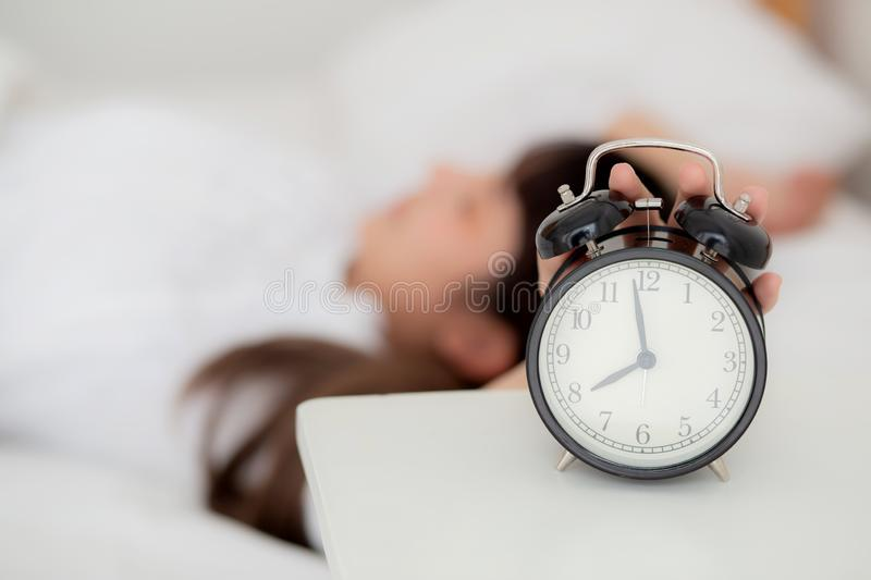 Beautiful asian young woman turn off alarm clock in morning, wake up for sleep with alarm clock. Relax and lifestyle concept stock photography