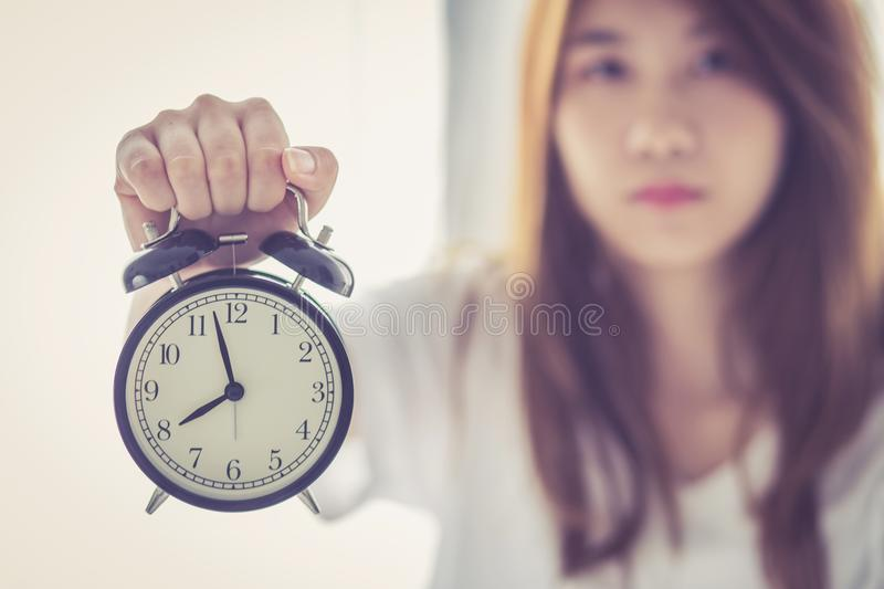 Beautiful asian young woman wake up in morning annoyed alarm clock holding hand stock photo