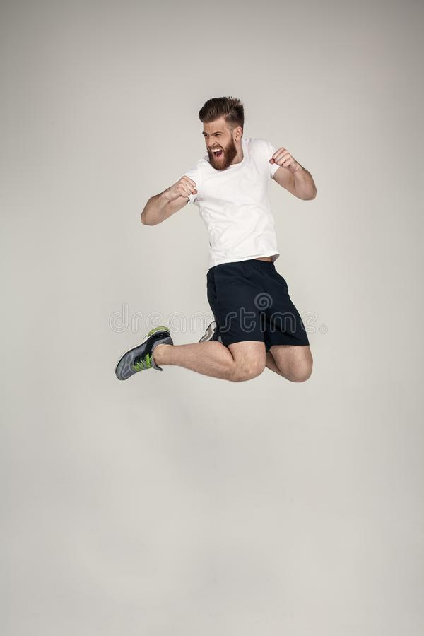 A beautiful athlete with a beard jumped up the hill in the studio. wearing sneakers and a white T-shirt. opposite the white wall stock photography