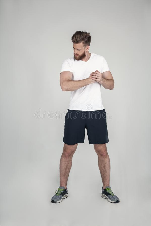 A beautiful athlete with a beard shows his muscles. looking at your biceps. dressed in sports shorts sneakers and a white T-shirt royalty free stock photo