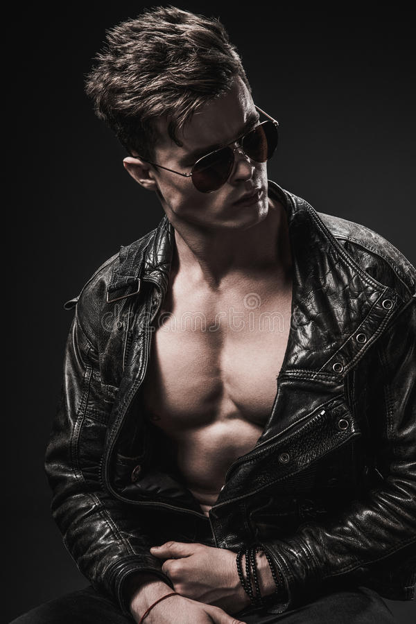 Beautiful athletic bodybuilder male model posing in studio. Expression on camera. Brutal man in leather suit. stock photo