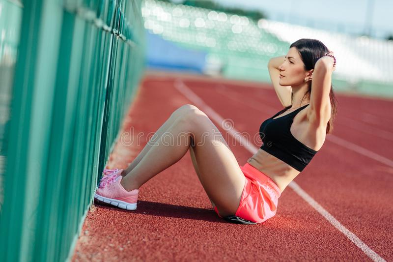 Beautiful athletic brunette woman in pink shorts and tank top working ab intervals in fitness. brunette young girl doing exercises stock photo