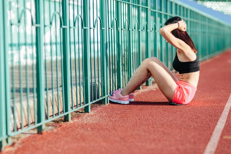 Beautiful athletic brunette woman in pink shorts and tank top working ab intervals in fitness. brunette young girl doing exercises. Beautiful athletic woman royalty free stock photos