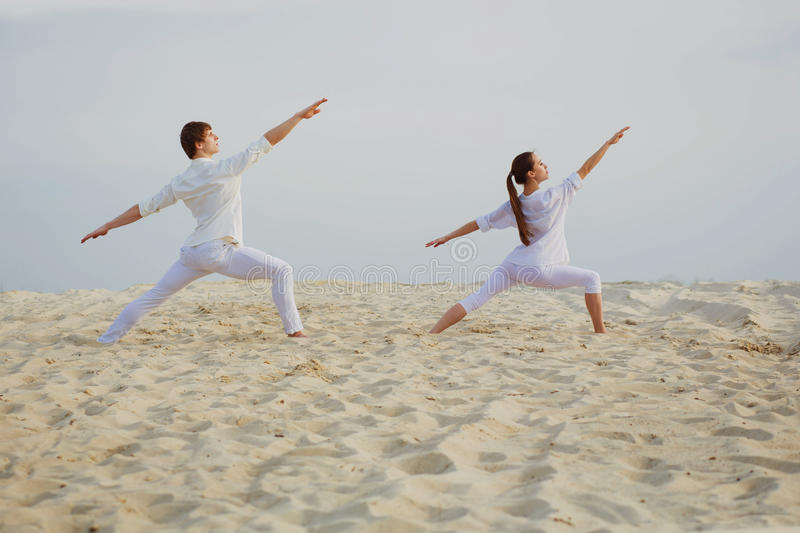 Beautiful, athletic couple in white clothes making yoga exercis. Healthy lifestyle concept. fitness, sport. beautiful, athletic couple in white clothes making royalty free stock image