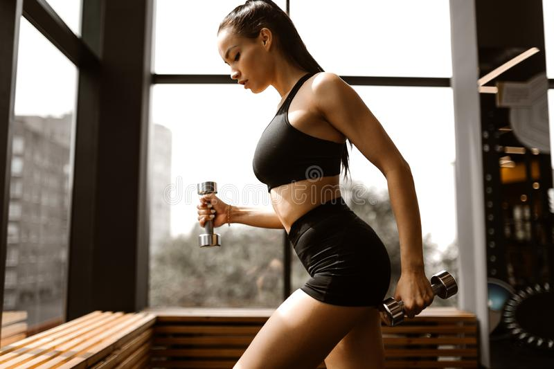 Beautiful athletic girl with brown hair dressed in black sports top and shorts holds dumbbells in the gym royalty free stock photos