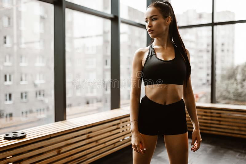 Beautiful athletic girl with brown hair dressed in black sports top and shorts stands in the gym royalty free stock photography
