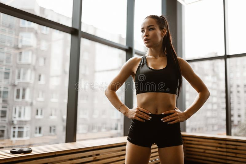 Beautiful athletic girl with brown hair dressed in black sports top and shorts stands in the gym royalty free stock photo