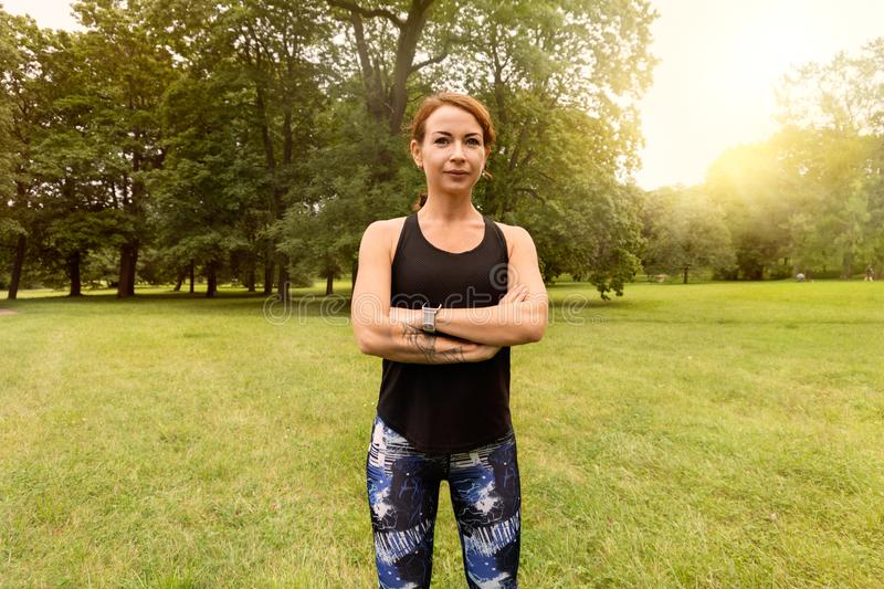 Beautiful and athletic girl with clothes for jogging standing with her hands crossed over her chest royalty free stock photo
