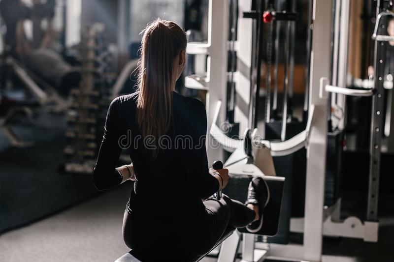 The beautiful athletic girl dressed dressed in a black sportswear is doing sport exercises with equipment on the bench stock images