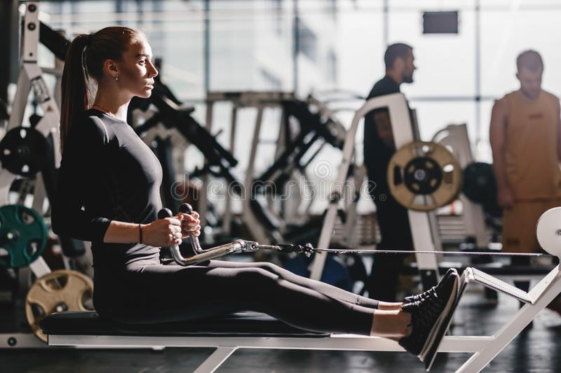 The beautiful athletic girl dressed dressed in a black sportswear is doing sport exercises with equipment on the bench stock image