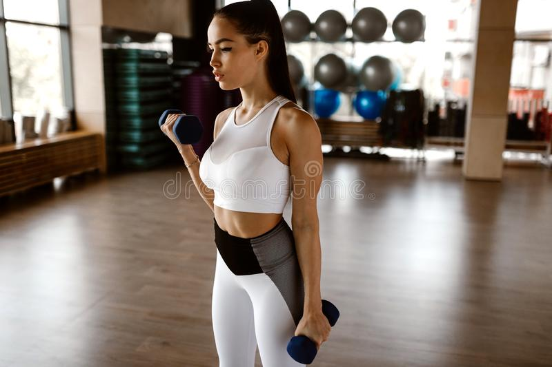 Beautiful athletic girl dressed in white sports top and tights builds up muscles with dumbbells royalty free stock photography