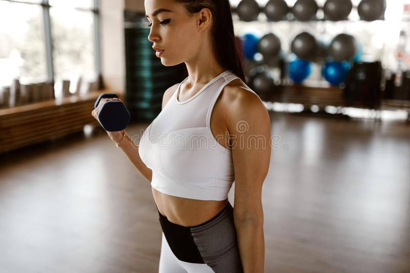 Beautiful athletic girl dressed in white sports top and tights builds up muscles with dumbbells royalty free stock photo