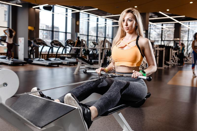 The beautiful athletic girl with long blond hair dressed in a sportswear is doing sport exercises with equipment on the stock image