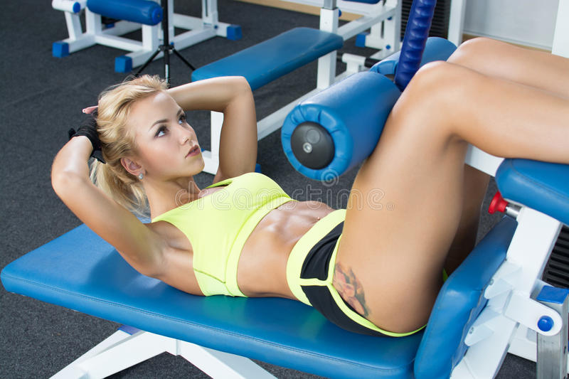 Beautiful athletic girl swings the press in the gym in the sport equipment. Weight Loss. Psychological struggle. stock photography