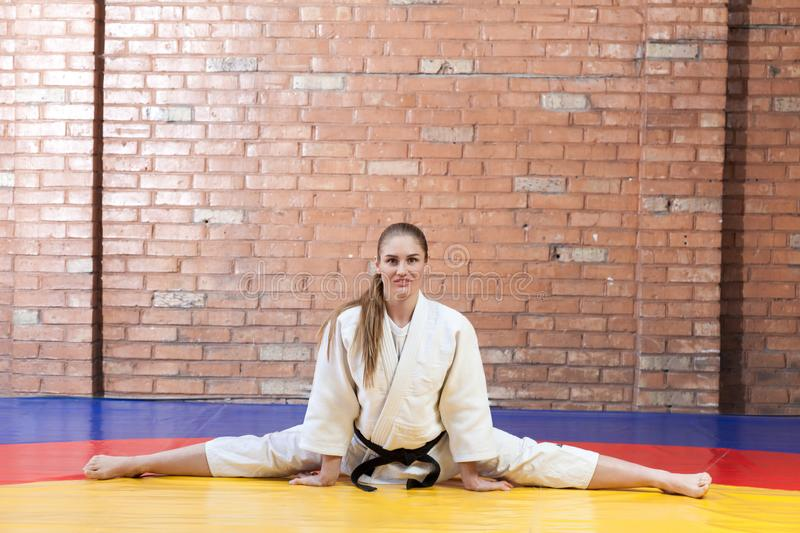 Beautiful athletic karate woman in white kimono with black belt stock images