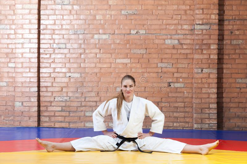 Beautiful athletic karate woman in white kimono with black belt. Stretching in twine and looking at camera. Japanese martial arts concept. Indoor, studio shot royalty free stock images