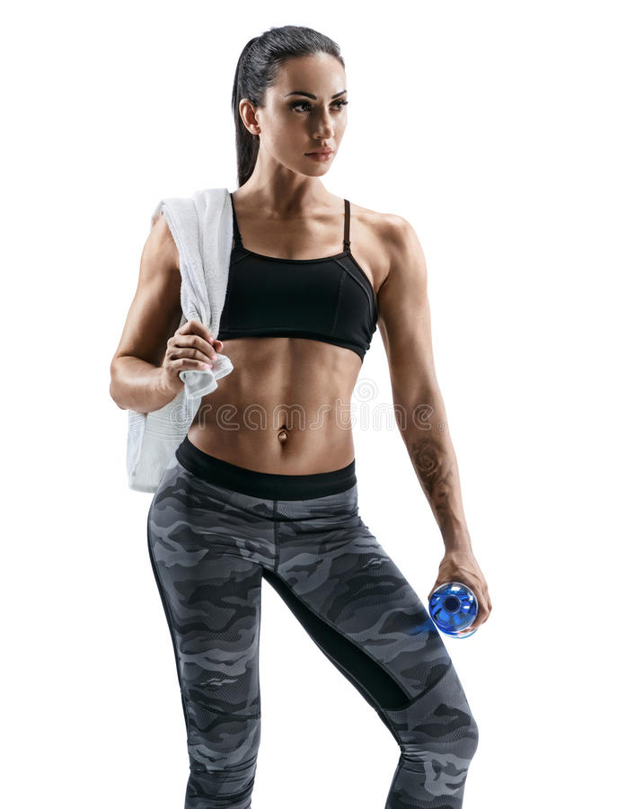 Beautiful athletic woman with towel on shoulders holding bottle of water royalty free stock image