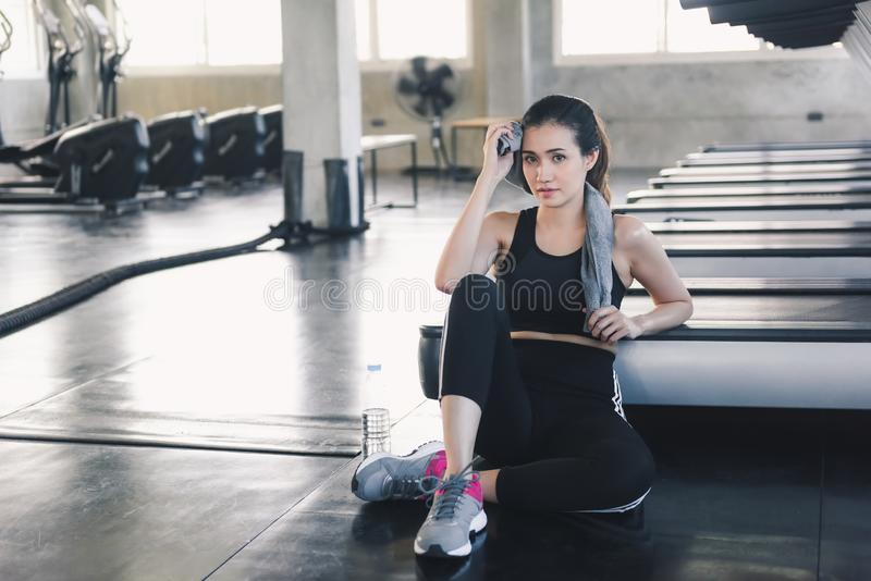 Beautiful Athletic Woman is Wiping Sweat With Towel After Exercised in Gym, Portrait of Pretty Girl in Sportswear is Exercising in stock images