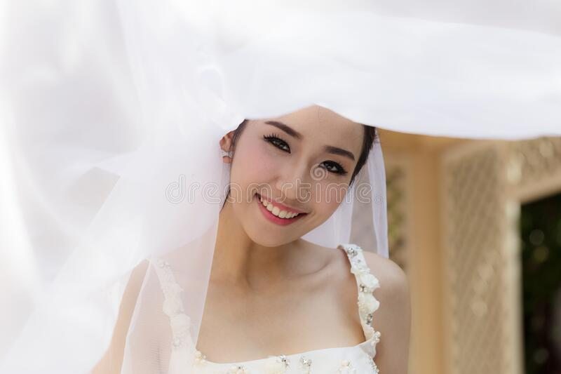 Beautiful Attractive Asian Bride Woman wearing white wedding dress and holding bouquet smile. So proud and happiness in wedding day,Bride Concept royalty free stock images
