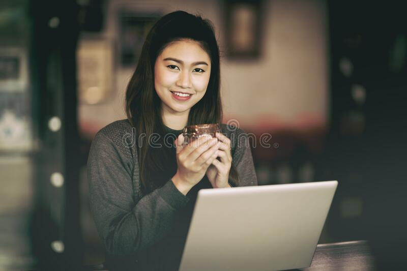 Beautiful Attractive Asian Business woman smile and holding coffee in Coffee shop cafe with computer laptop on the table. Feeling so happiness and comfortable royalty free stock photo