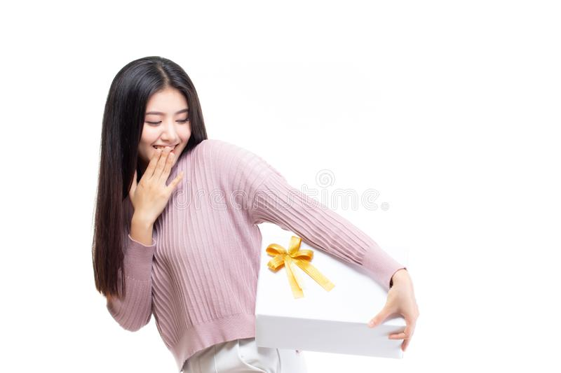 Beautiful attractive asian woman holding gift box in christmas, new year, valentine day, birthday celebration concept. Portrait of royalty free stock photo