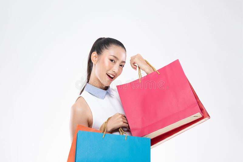 Beautiful Attractive Asian Woman smile and holding shopping bags feeling so happiness and enjoy with black Friday sale in Shopping royalty free stock photography