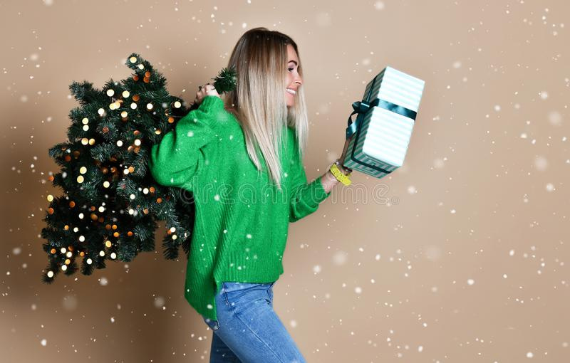 Beautiful attractive blond hair woman carry Christmas fir tree with bokeh lights and gift box in green sweater under snow royalty free stock photo